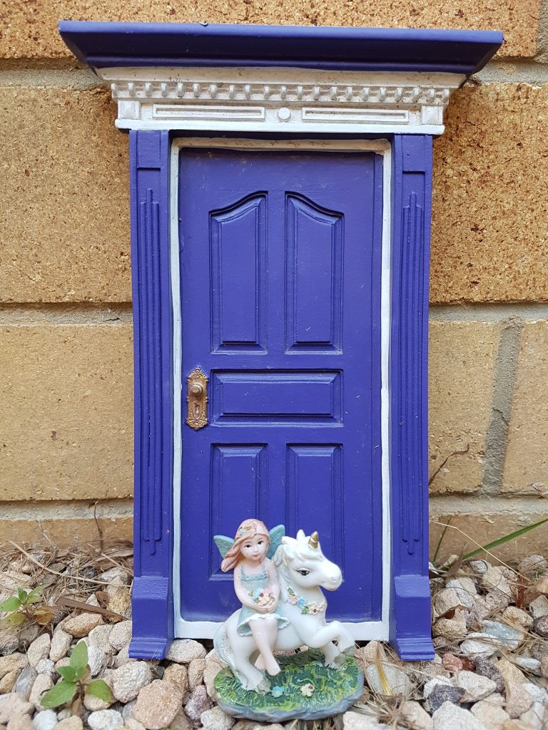 Purple fairy door and toy fairy
